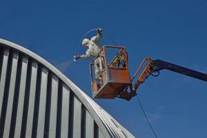 27931152 - tradesman spray painting the roof of an industrial building