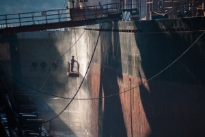 58969922 - shipyard worker power washing a ship on dry dock